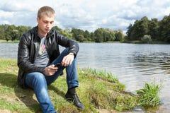 Blonder Mann in der schwarzen Lederjacke, die in der Hand auf Flussbank mit Handy sitzt Stockfoto