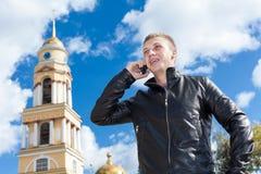 Blonder Mann in der schwarzen Lederjacke nennend mit Handy in der russischen Stadt Stockfotos