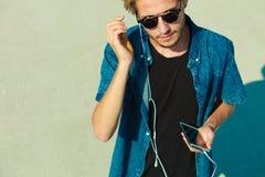 Blonder Mann in der Sonnenbrille hörend Musik Lizenzfreies Stockbild