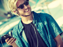 Blonder Mann in der Sonnenbrille hörend Musik Stockfoto
