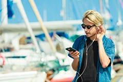Blonder Mann in der Sonnenbrille hörend Musik Lizenzfreies Stockfoto