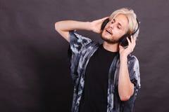 Blonder Mann, der in tragenden Kopfhörern des Studios singt Lizenzfreie Stockbilder