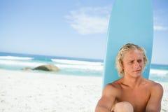 Blonder Mann, der vor seinem Surfbrett beim Blicken in Richtung der Seite sitzt Lizenzfreie Stockbilder