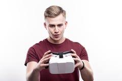 Blonder Mann, der VR-Kopfhörer mit Überraschung betrachtet Stockfoto