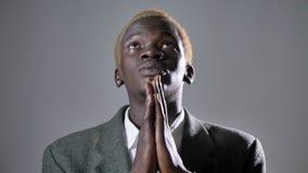 Blonder Mann des jungen Afroamerikaners im Klagenhändchenhalten und -c$beten, lokalisiert auf grauem Hintergrund stock video footage