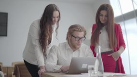 Blonder Mann des Porträts in den Gläsern, die in einem hellen bequemen Büro mit netbook am Tisch sitzen Zwei Mädchen in der forme stock video