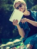 Blonder Mann draußen unter Verwendung seiner Tablette draußen Lizenzfreie Stockbilder