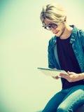 Blonder Mann draußen unter Verwendung seiner Tablette draußen Stockfotos