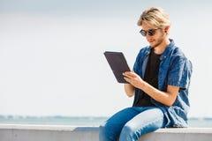 Blonder Mann draußen unter Verwendung seiner Tablette draußen Lizenzfreies Stockfoto