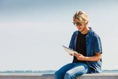 Blonder Mann draußen unter Verwendung seiner Tablette draußen Stockbilder