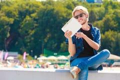 Blonder Mann draußen unter Verwendung seiner Tablette draußen Lizenzfreie Stockfotografie