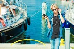 Blonder Mann draußen unter Verwendung seines Smartphone Stockbilder