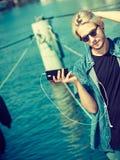 Blonder Mann draußen unter Verwendung seines Smartphone Lizenzfreies Stockbild