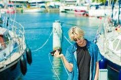 Blonder Mann draußen unter Verwendung seines Smartphone Lizenzfreie Stockbilder