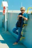 Blonder Mann draußen unter Verwendung seines Smartphone Stockfoto