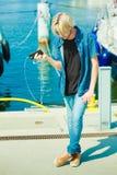 Blonder Mann draußen unter Verwendung seines Smartphone Stockbild