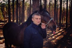 Blonder Mann und Pferd Des Herbstes Sonnenlichtszene draußen stockfoto