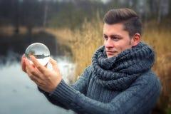 Blonder Mann vor dem See, der eine Glaskugel hält Lizenzfreies Stockfoto