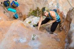 Blonder netter Bergsteiger auf felsigem Gelände trifft schwierige Maßnahme Lizenzfreie Stockfotos