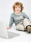 Blonder Rotationhaarjunge, der nahe Laptop setzt Lizenzfreie Stockfotografie