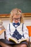 Blonder Schüler, der ein Buch liest Stockbild