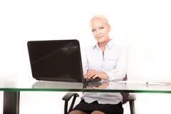 Blonder Sekretär, der an einem Laptop arbeitet Lizenzfreie Stockfotografie