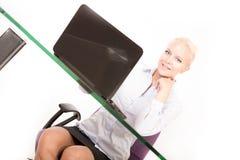 Blonder Sekretär, der an einem Laptop arbeitet Stockbild