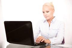 Blonder Sekretär, der an einem Laptop arbeitet Lizenzfreies Stockfoto