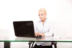 Blonder Sekretär, der an einem Laptop arbeitet Lizenzfreies Stockbild