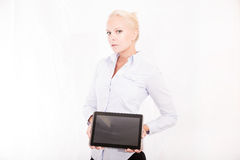 Blonder Sekretär, der einen Tabletten-PC hält Stockbild