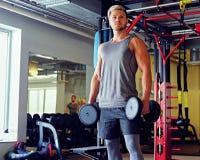 Blonder sportlicher Mann, der Hocken mit Dummköpfen in einem Turnhallenclub tut Lizenzfreies Stockfoto