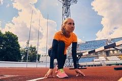 Blonder sportlicher weiblicher Läufer in schnelles Anfangsposition Stockfoto