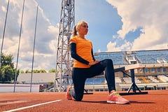 Blonder sportlicher weiblicher Läufer in schnelles Anfangsposition Stockbilder