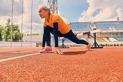 Blonder sportlicher weiblicher Läufer in schnelles Anfangsposition Stockfotografie
