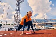 Blonder sportlicher weiblicher Läufer in schnelles Anfangsposition Lizenzfreie Stockfotos