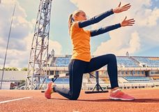 Blonder sportlicher weiblicher Läufer in schnelles Anfangsposition Lizenzfreie Stockfotografie