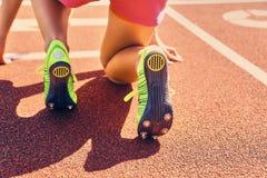 Blonder sportlicher weiblicher Läufer in schnelles Anfangsposition Lizenzfreie Stockbilder