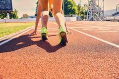 Blonder sportlicher weiblicher Läufer in schnelles Anfangsposition Stockbild