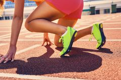 Blonder sportlicher weiblicher Läufer in schnelles Anfangsposition Lizenzfreies Stockbild