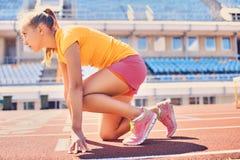 Blonder sportlicher weiblicher Läufer in schnelles Anfangsposition Lizenzfreies Stockfoto