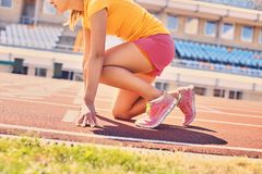 Blonder sportlicher weiblicher Läufer in schnelles Anfangsposition Stockfotos