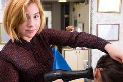 Blonder Stilist-trocknendes Haar der Frau mit Schlag-Trockner Lizenzfreie Stockfotos