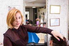 Blonder Stilist-trocknendes Haar der Frau mit Schlag-Trockner Stockfotos