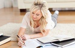 Blonder Student, der auf dem Fußbodenlernen liegt Lizenzfreie Stockfotos