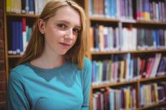 Blonder Student in der Bibliothek, welche die Kamera betrachtet Lizenzfreie Stockfotos
