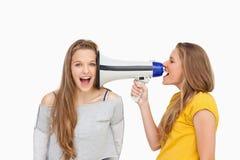 Blonder Student, der einen Lautsprecher auf ihrem Freund verwendet Stockfoto