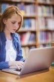 Blonder Student, der Laptop in der Bibliothek verwendet Lizenzfreie Stockfotografie