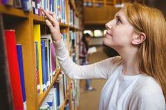 Blonder Student, der nach Buch in den Bibliotheksregalen sucht Lizenzfreie Stockfotografie