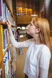 Blonder Student, der nach Buch in den Bibliotheksregalen sucht Stockfoto