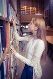 Blonder Student, der nach Buch in den Bibliotheksregalen sucht Lizenzfreies Stockfoto